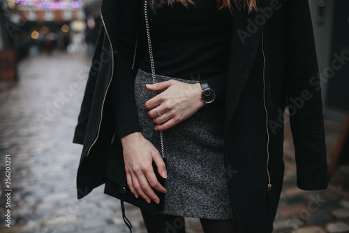 A young fashionable woman under rain wearing black top, black coat and grey skirt. Concept of street style, blogging and lifestyle. Horizontal image with selective focus on the details of the outfit. © Olga