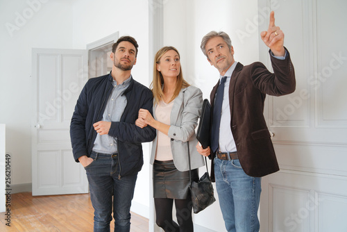 Leinwanddruck Bild Couple with real-estate agent visiting light contemporary house