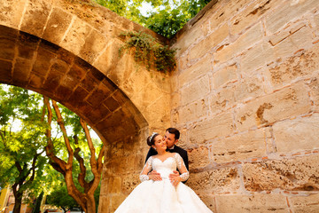 Happy wedding couple posing in park under old arch