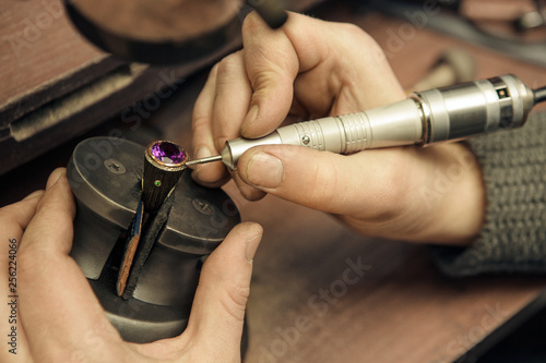 Close up of a jeweler repairing a ring with violet gemstone © Nestor
