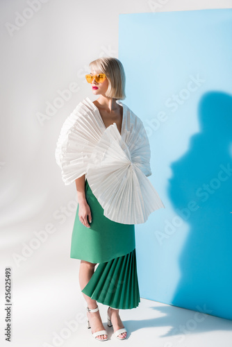 Leinwanddruck Bild attractive stylish girl in sunglasses and paper clothes posing on blue and grey