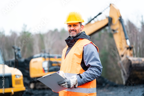 Portrait of a quarry worker standing in front of excavator