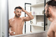 Leinwanddruck Bild - handsome shirtless man touching hair and holding toothbrush with toothpaste while looking at mirror in bathroom
