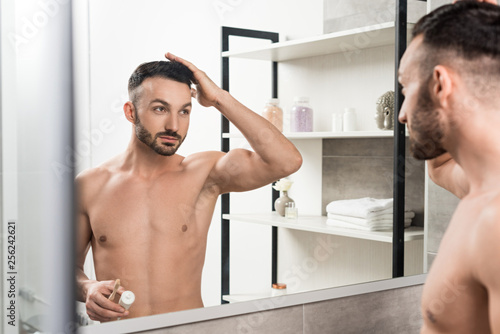 Leinwanddruck Bild handsome shirtless man touching hair and holding toothbrush with toothpaste while looking at mirror in bathroom