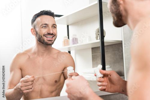 Leinwanddruck Bild happy bearded man holding dental floss while looking at mirror in bathroom