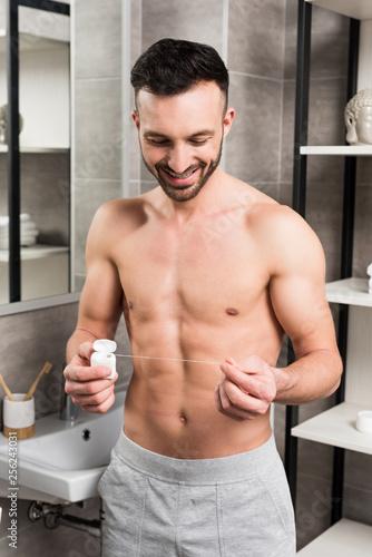 Leinwanddruck Bild happy shirtless man looking at dental floss while standing in bathroom