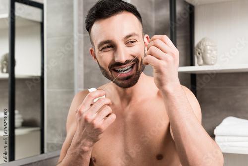 Leinwanddruck Bild bearded man using dental floss while standing in bathroom