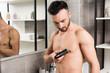 Leinwanddruck Bild - handsome shirtless man holding trimmer while shaving torso in bathroom