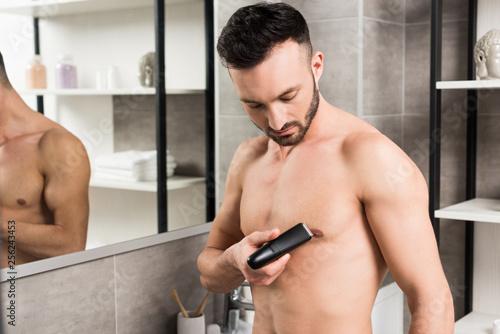 Leinwanddruck Bild handsome shirtless man holding trimmer while shaving torso in bathroom
