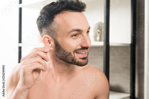 Leinwanddruck Bild cheerful shirtless man cleaning ear while looking at mirror in bathroom