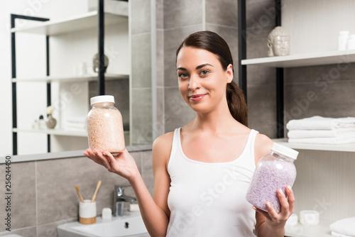 Leinwanddruck Bild cheerful brunette woman holding glass jars with sea salt in bathroom