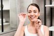 Leinwanddruck Bild - happy brunette woman using dental floss in bathroom
