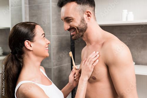Leinwanddruck Bild cheerful brunette girlfriend holding toothbrush while hugging happy shirtless boyfriend in bathroom