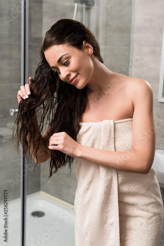 Leinwanddruck Bild cheerful woman touching wet hair while standing in bathroom