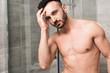 Leinwanddruck Bild - handsome muscular man touching hair in modern bathroom
