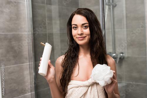 Leinwanddruck Bild cheerful brunette woman holding shower gel and loofah in hands