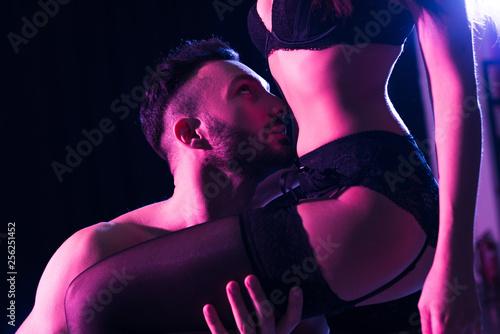 Leinwandbild Motiv sexy shirtless man kissing body of sexy girlfriend standing in underwear isolated on black