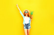 Leinwanddruck Bild - Happy smiling woman raises her hands up with pineapple having fun in summer straw hat, sunglasses, shorts on colorful yellow background