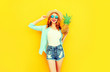 Leinwanddruck Bild - Happy smiling woman with pineapple having fun in summer straw hat, sunglasses, shorts on colorful yellow background