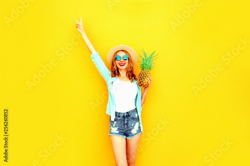 Leinwanddruck Bild Happy smiling woman raises her hands up with pineapple having fun in summer straw hat, sunglasses, shorts on colorful yellow background