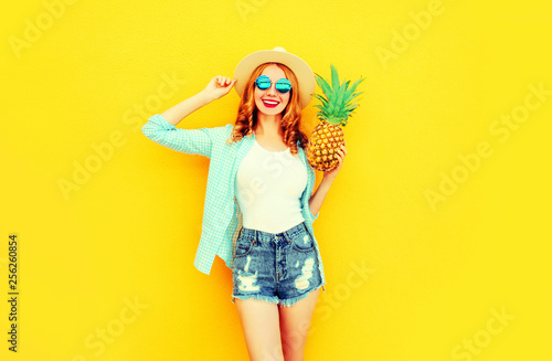 Leinwanddruck Bild Happy smiling woman with pineapple having fun in summer straw hat, sunglasses, shorts on colorful yellow background