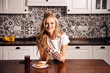 Adorable blonde girl in pajama enjoying hot coffee in modern light white kitchen interior