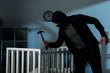 Leinwanddruck Bild - Criminal in mask holding hammer while standing near crib in dark room