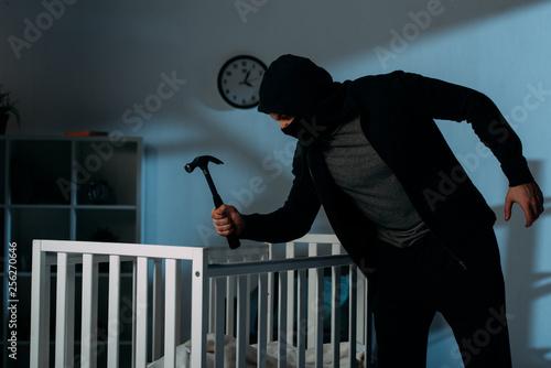 Leinwanddruck Bild Criminal in mask holding hammer while standing near crib in dark room