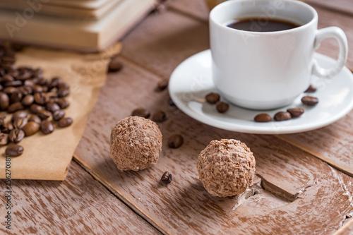 Leinwanddruck Bild Coffee time break. Cup of freshly breved turk coffee, chocolate balls and book on wooden table