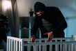 Leinwanddruck Bild - Criminal in mask and black clothes kidnapping child from crib