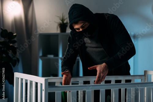 Leinwanddruck Bild Criminal in mask and black clothes kidnapping child from crib