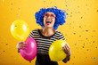 Happy woman with blue hair holding colorful balloons