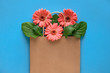 Quadro Coral gerbera daisy flowers in craft papper shopping bag on blue paper background, copy-space