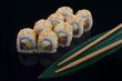 sushi roll with sesame on black background