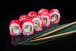 sushi roll with flying fish roe on black background
