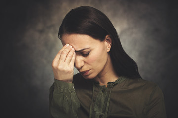 Young woman has headache on a grungy background © Minerva Studio