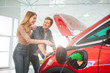 Leinwanddruck Bild - Young smiling family buying first electric car in the showroom. Attractive pleasantly surprised woman point at eco-friendly car battery while standing near her husband. Electric car sale concept