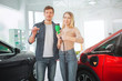 Leinwanddruck Bild - Young smiling family buying first electric car in the showroom. Environmental protection. Attractive man and woman holding car key and electric car charging plug. Green electric car sale concept