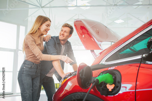 Leinwanddruck Bild Young smiling family buying first electric car in the showroom. Attractive pleasantly surprised woman point at eco-friendly car battery while standing near her husband. Electric car sale concept