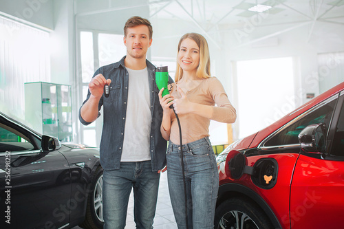 Leinwanddruck Bild Young smiling family buying first electric car in the showroom. Environmental protection. Attractive man and woman holding car key and electric car charging plug. Green electric car sale concept