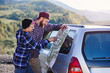 Happy tourist couple with paper map near car. Smiling young people using map. Traveling by rented car on summer vacations. Hipster man and woman having trip outdoors in mountains.