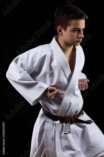 Karate martial sport with young boy in kimono,  black background,   activity.