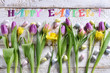 easter flat lay with a row of colorful flowers eggs and wishes text