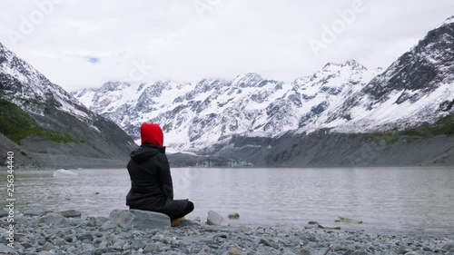 Unrecognizable person in hoodie sitting by rippling glacial lake in valley at the foot of snow-capped mountain ranges
