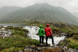 Couple of tourists standing by the mountain river on a foggy summer day in the rain