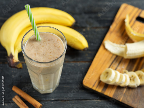 Banana smoothie with cinnamon in glass on wooden background © pavelkant
