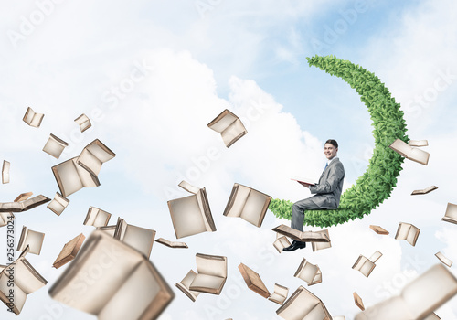 Man reading book and many of them flying in air