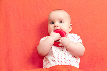 Infant chews teething ring against living coral trendy color background