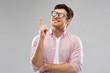 education, idea and people concept - smiling young man in glasses pointing finger up over grey background