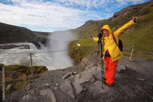 Woman in bright yellow and red clothes making photos in amazing Detifoss waterfall, Iceland
